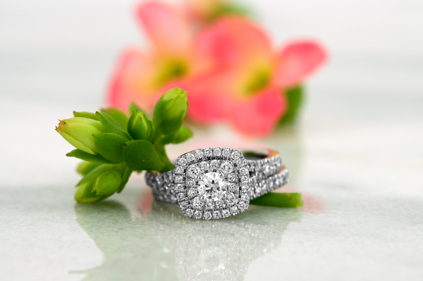 Diamond engagement ring with green and pink flowers on a marble surface